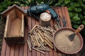 1/ Benodigdheden: een oud nestkastje zonder voorzijde, bamboestukjes, een stuk dikke tak, leem en een boormachine met houtboren.